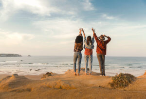 women raising hands beach medication assisted treatment rehab