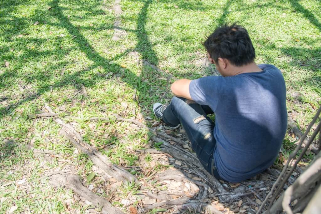 dark haired man crouching grass borderline personality disorder rehab
