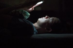 addicted to internet man lying down and playing mobile phone