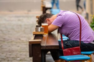 sleeping man at a table next to the beer cup brew craft problem with alcohol