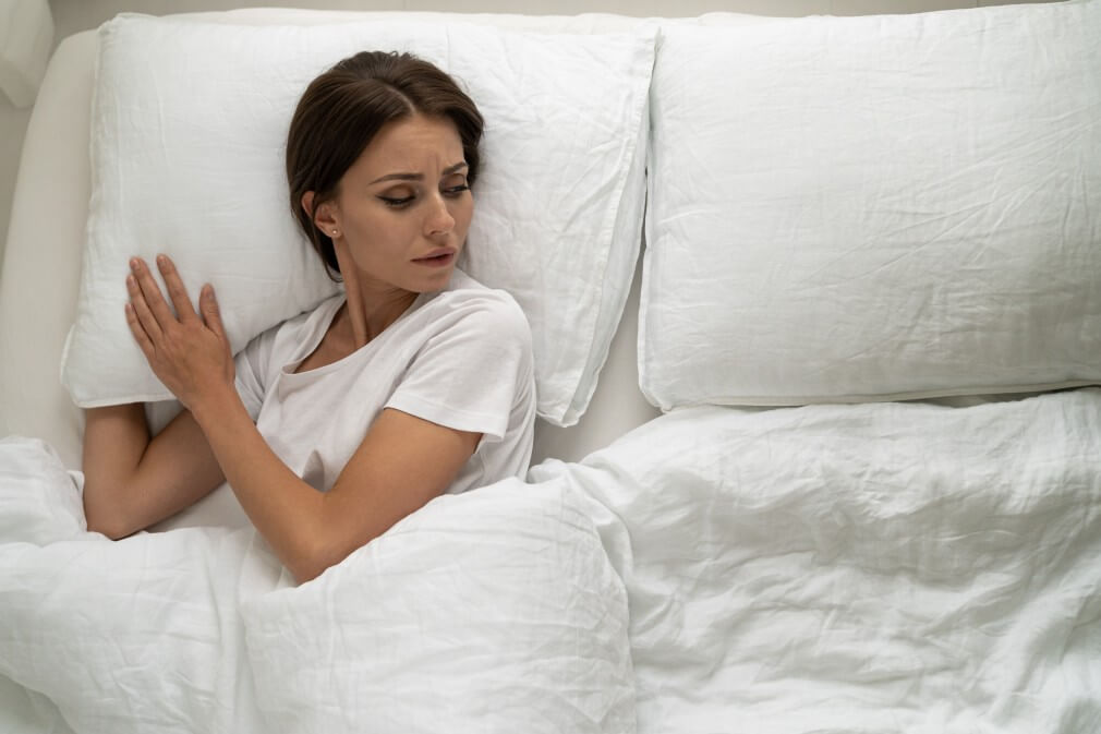 forgiving and moving on top view of sad woman lying in bed alone looking to aside at an empty pillow depressed feeling lonely