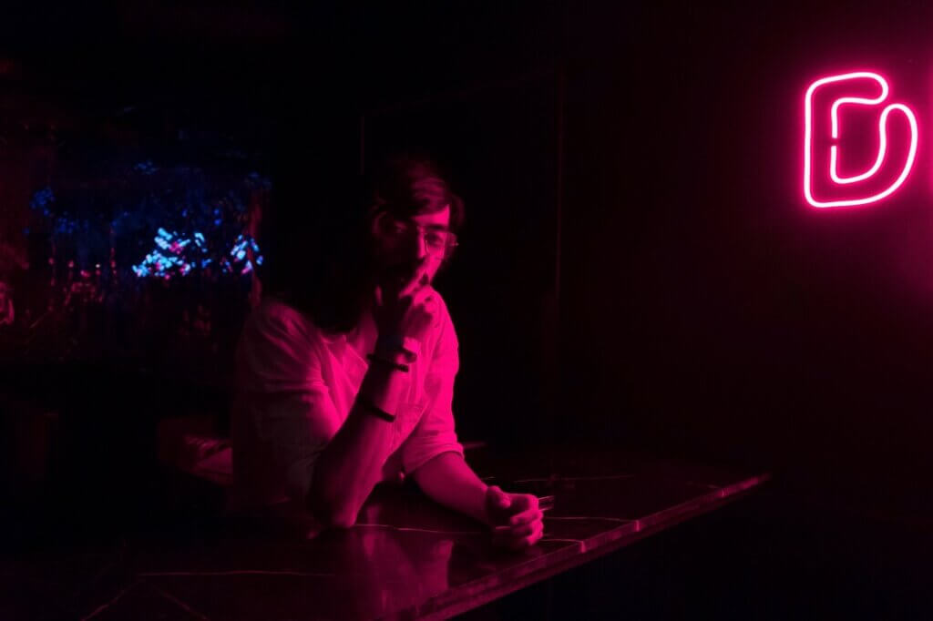 hitting rock bottom when will an addict stop a drunk young adult looking straight while sitting inside a night club under a neon disco light sign