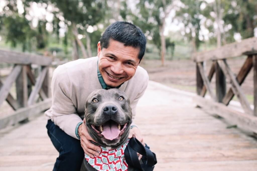 a man posing with his dog pets emotional health support bridge
