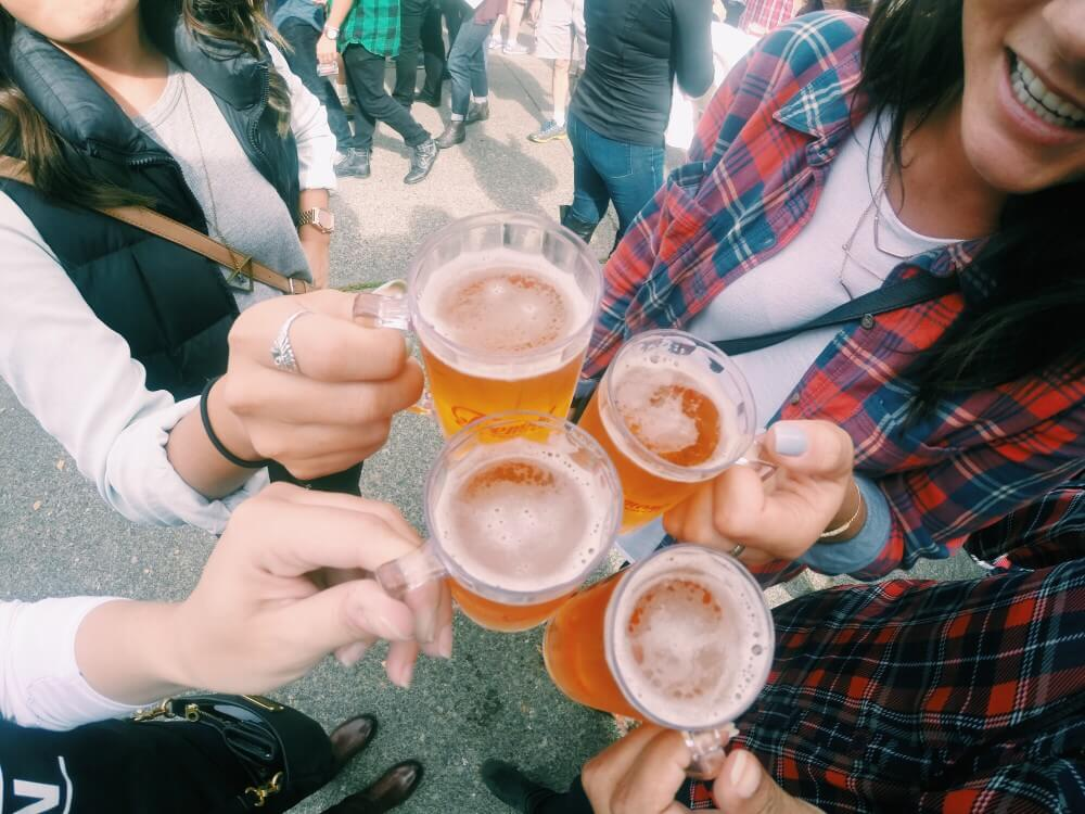 four smiling millennial women holding cups of beer wearing flannels in a crowd at a festival beer drinking excessively covid jump too much alcoholic