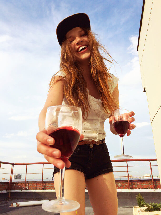 sunny girl drinking red wine on the rooftop alcoholic drinks increase consumption abuse help rehabilitation