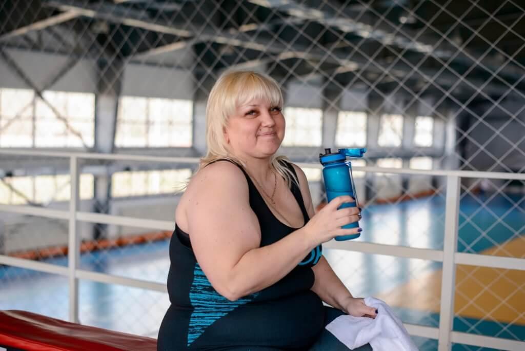 fat woman drinking water from a bottle in the gym fat woman in the gym weight loss woman with excess fears stigma
