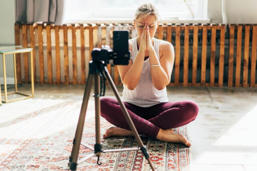 meditation retreats life changing yogi woman sitting at home on the floor meditates and records a meditation lesson on a mobile phone